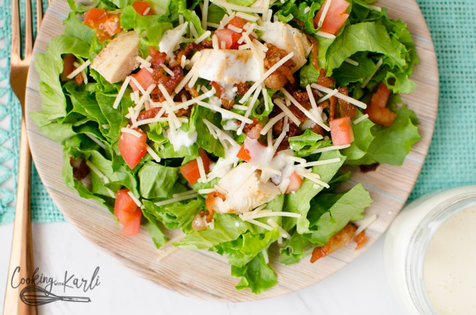 green lettuce salad topped with chicken, bacon, tomatoes and a homemade creamy sauce.
