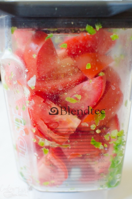 The fresh tomatoes in the blender before bing pulsed.