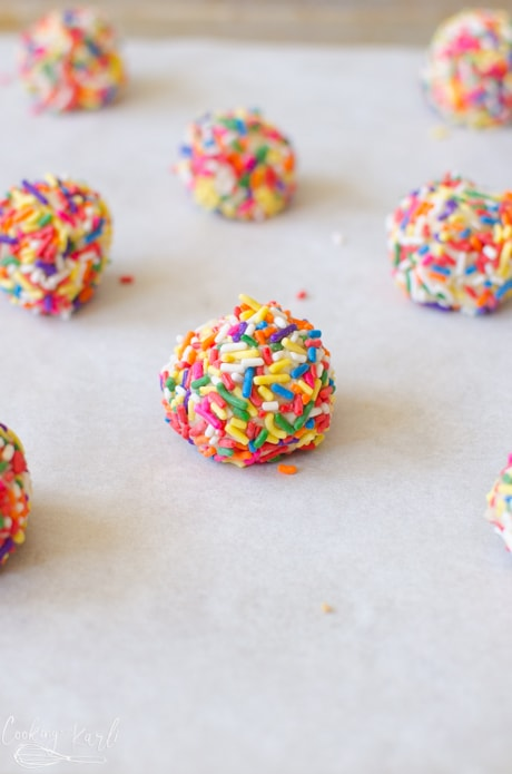 The sugar cookies covered with sprinkles before they are baked.