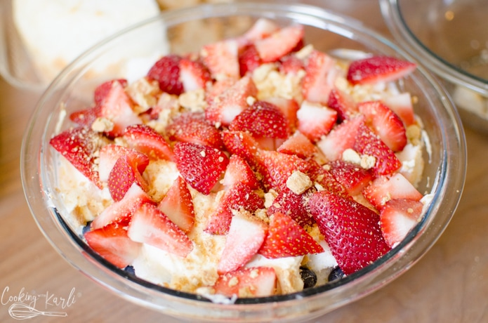 The top layer of the trifle is made up of sliced strawberries.