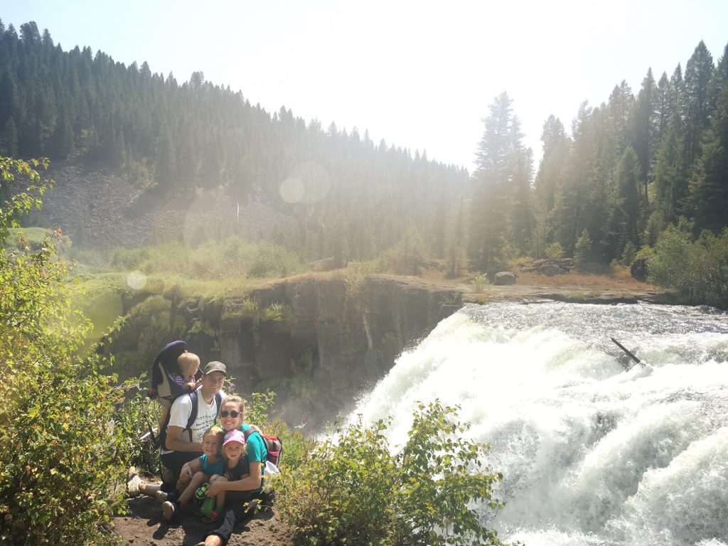 family sitting next to a waterfall