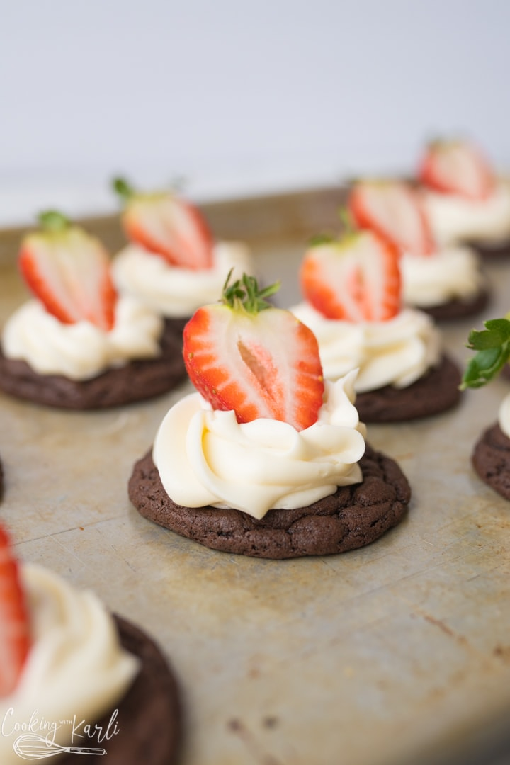chocolate cookie with cream cheese frosting and a strawberry.