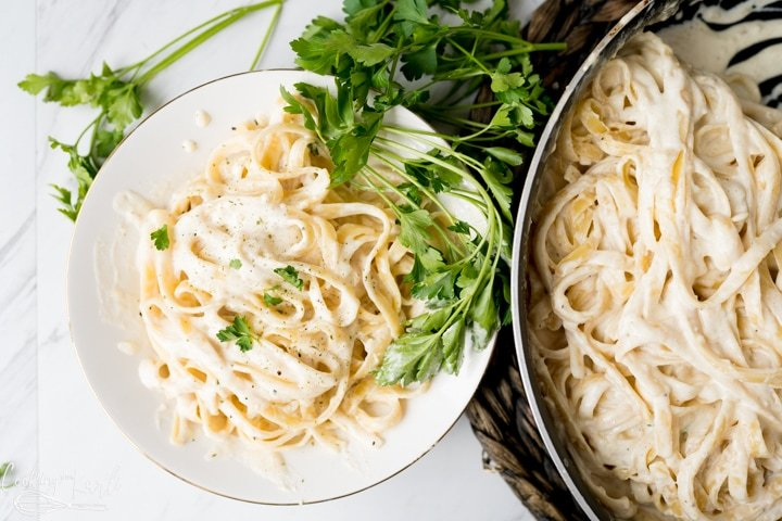 homemade Alfredo sauce, finished and served over fettuccine pasta
