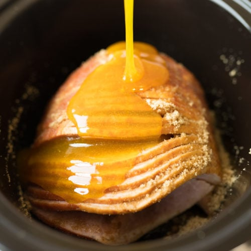 ham in the crockpot with glaze being poured on it.