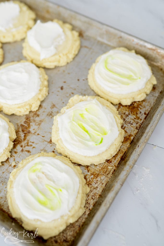 coconut lime cookies being frosted while on the pan