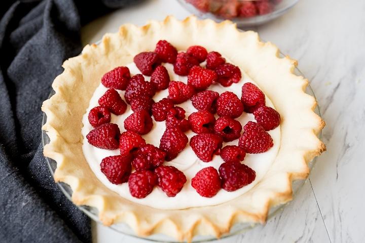 layering the raspberries and cream pie