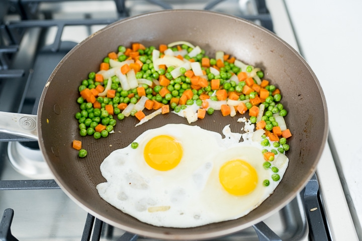 fried rice in the pan, showing how to scramble the eggs