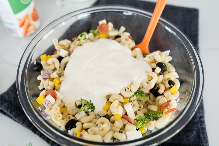 adding the dressing to the pasta salad