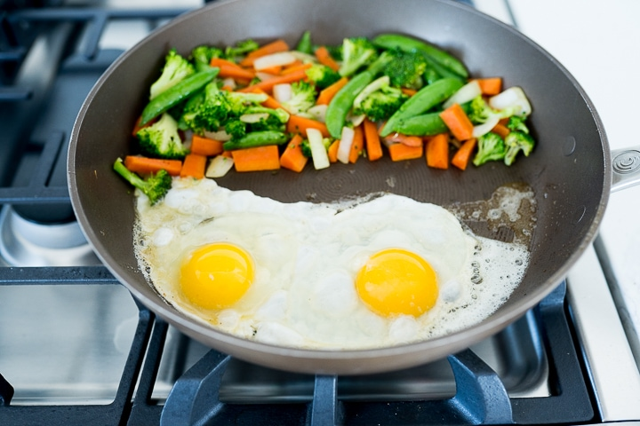 eggs being scrambled while veggies roast in the same pan.