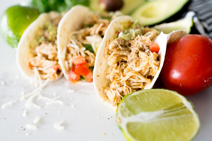 shredded chicken with honey lime sauce inside of a tortilla to make a taco