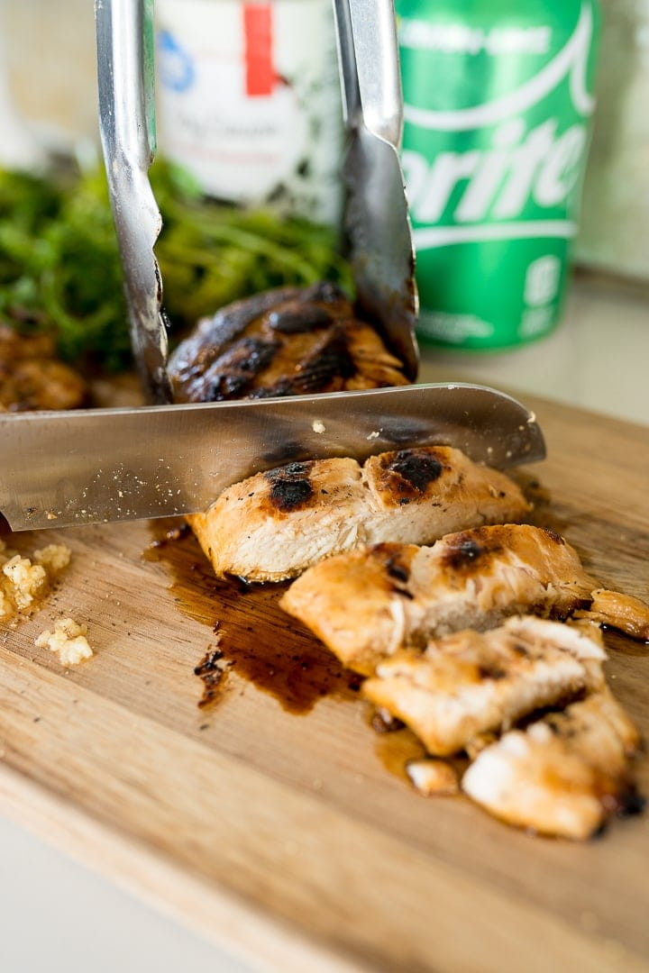Grilled chicken marinated in sprite and soy sauce, being cut up.