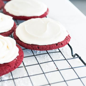 red velvet cookie on cooling rack with cream cheese frosting