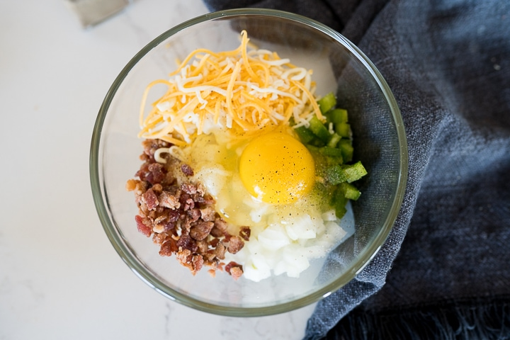 an egg, hashbsrowns, peppers, onions, bacon bits and cheese inside of a microwave safe bowl.