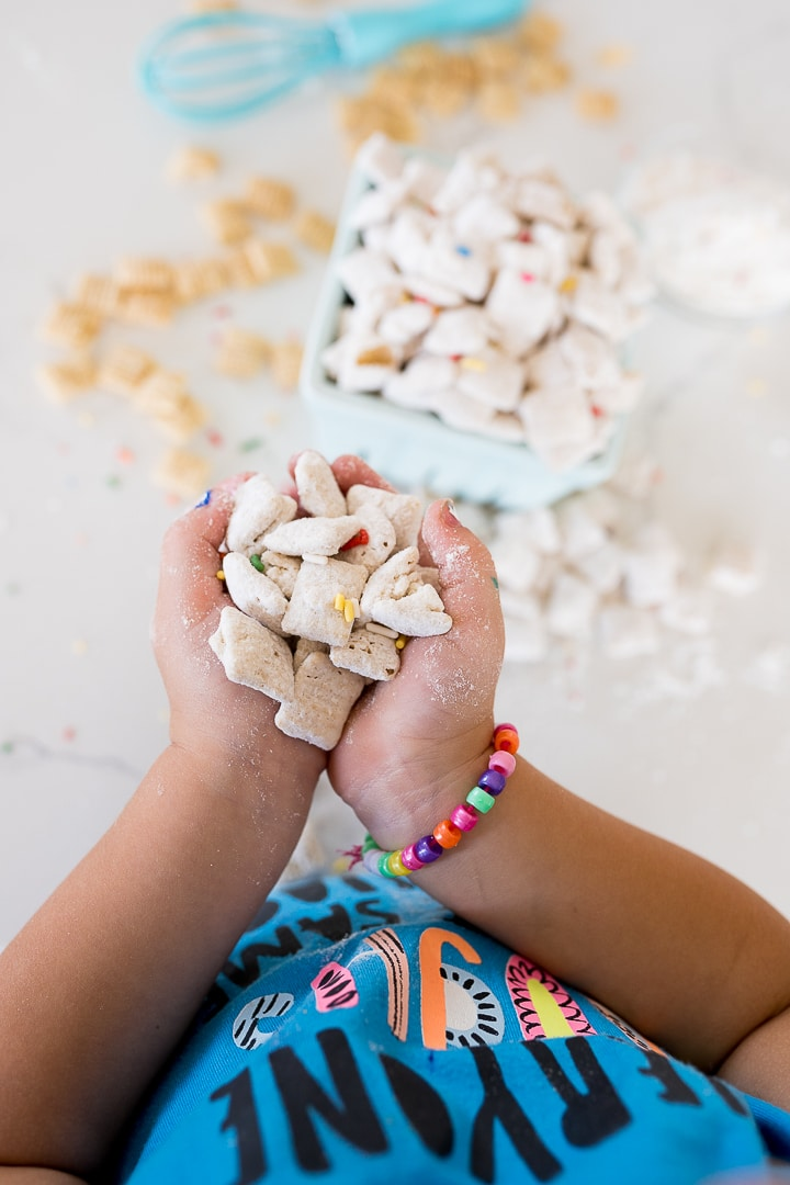 funfetti muddy buddies with sprinkles in small hands