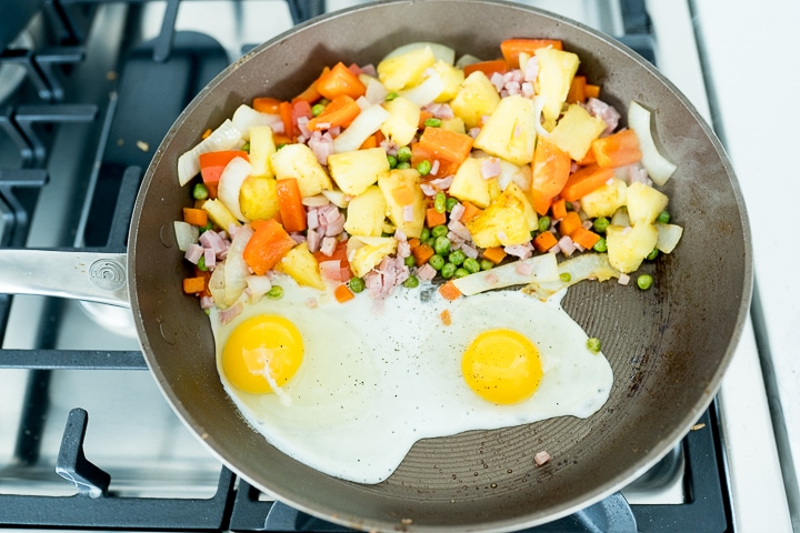 showing scrambling the eggs in the same pan that is holding the veggies.