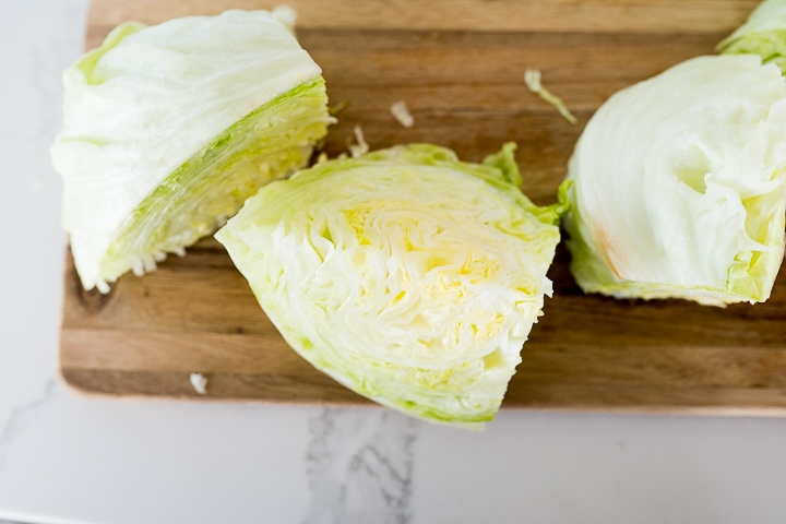 cutting a head of iceberg lettuce into wedges for a wedge salad