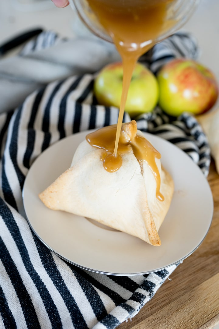 caramel being poured on an apple dumpling on a white plate with a striped towel.