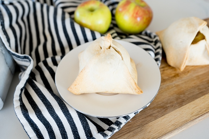cooked apple dumpling on a white plate, before caramel has been drizzled