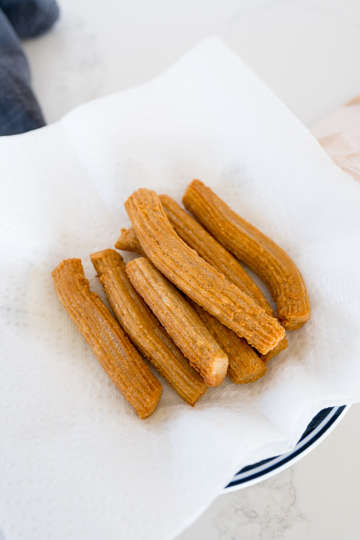 churros resting on a paper towel covered plate