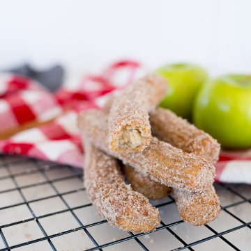 Cinnamon and sugar churros stacked on a cooling rack with apples in the background
