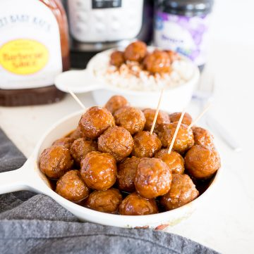 Grape jelly meatballs in a large plate/bowl with bbq sauce and grape jelly in the background