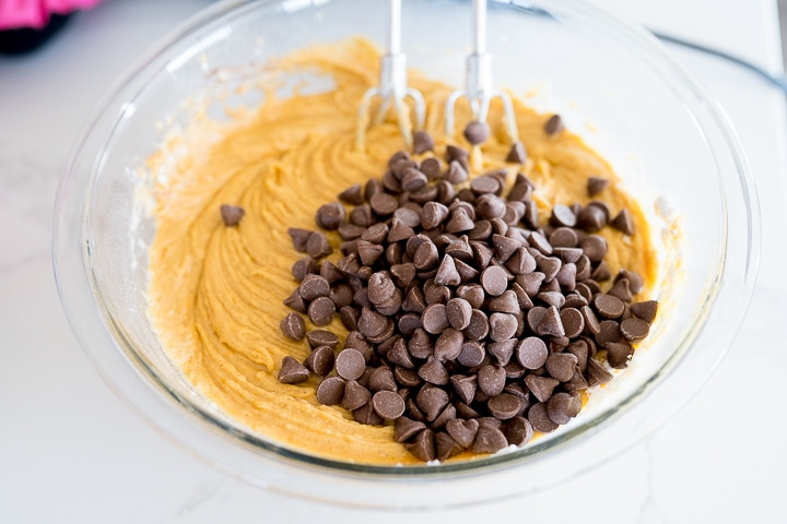 Chocolate chips being added to the pumpkin bread batter