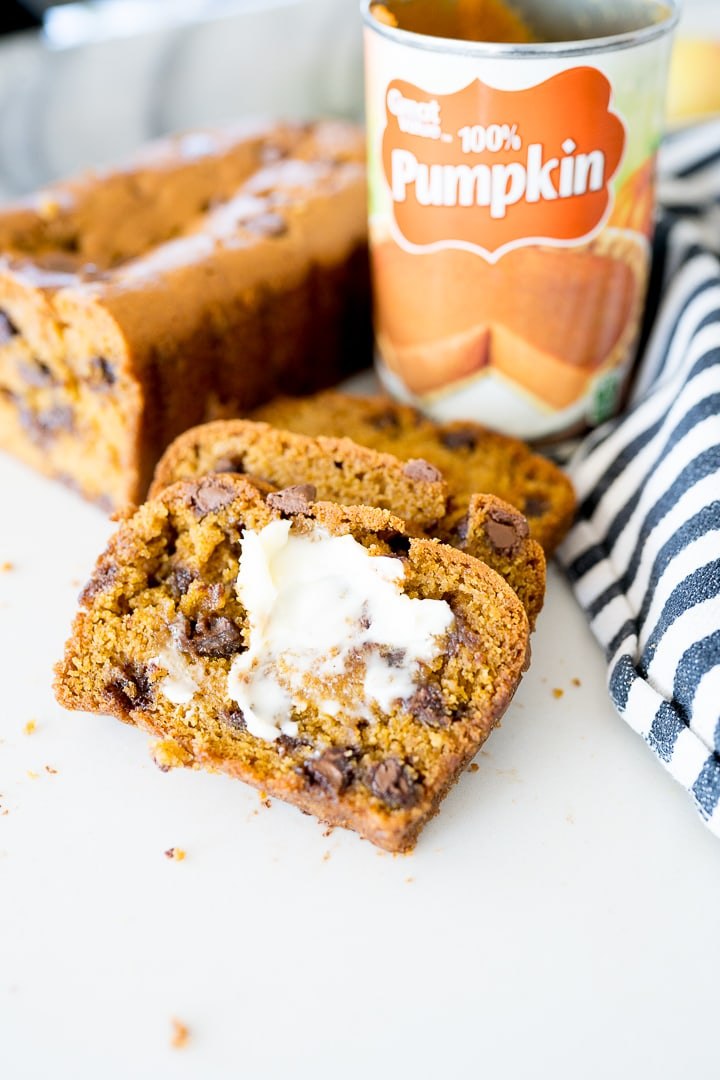 pumpkin chocolate chip bread, sliced with butter on it
