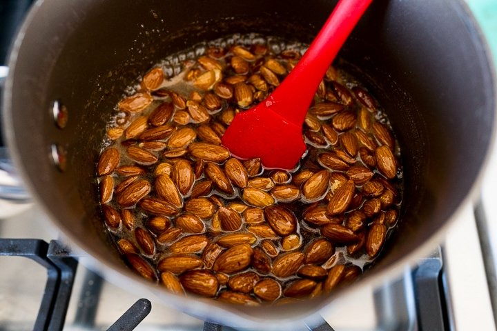 almonds in a sauce pan, in the process of being sugared.