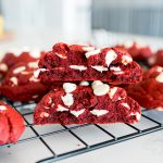 red velvet cookie with white chocolate chips, broken in half and stacked on top of each other