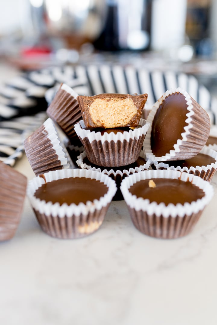 Homemade peanut butter cups, stacked on each other. One with a bite taken out.