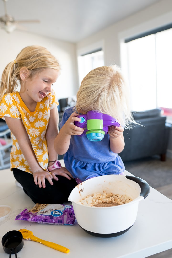 two young girls on the counter in front of a bowl of marshmallows