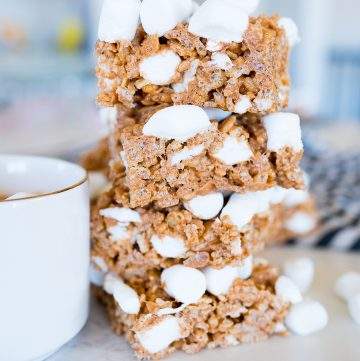Rice Krispies that are hot chocolate flavored stacked on top of each other next to a cup of cocoa