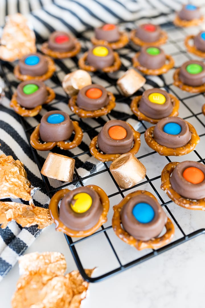 pretzels with rolo's and m&m's on top on a black cooling rack