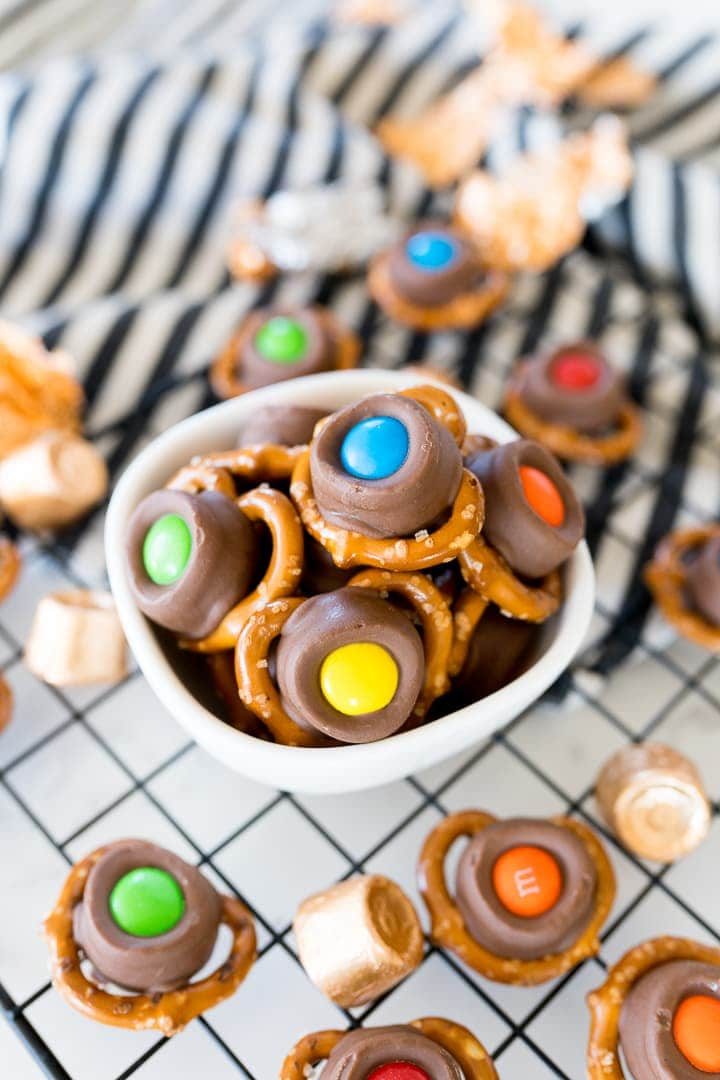 pretzels with rolls and m&m's on top in a small bowl