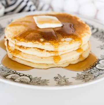 Buttermilk pancakes, stacked on a plate with syrup and butter on top