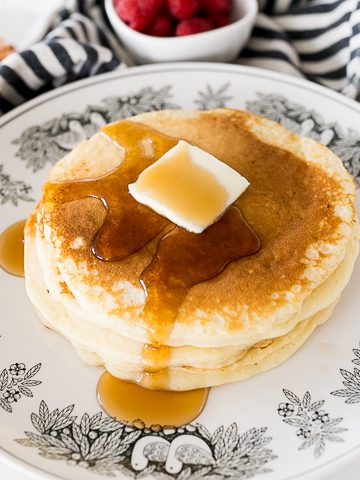 buttermilk pancakes stacked with maple syrup