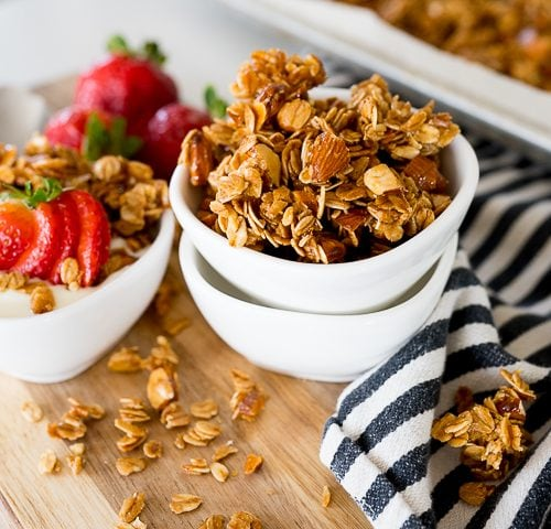 Homemade granola in a white bowl with strawberries