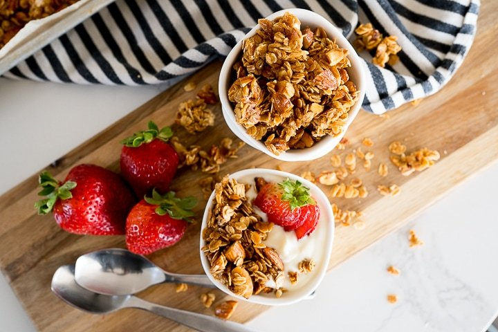 homemade granola in white bowls with strawberries and yogurt