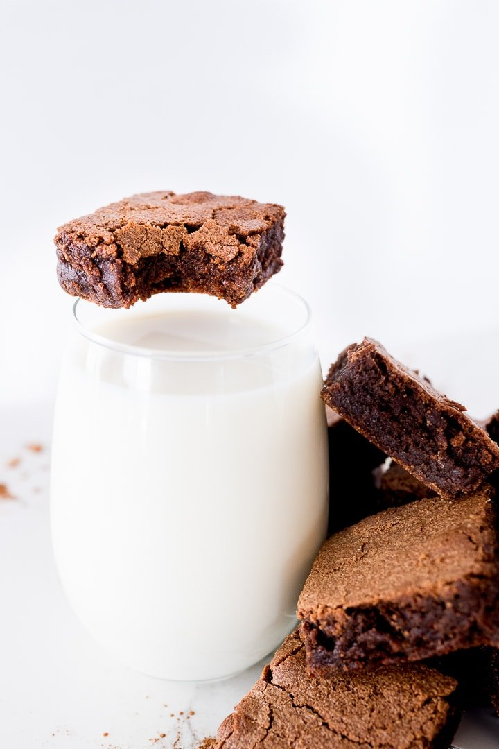 chocolate brownie with a bite taken out of it with a glass of milk