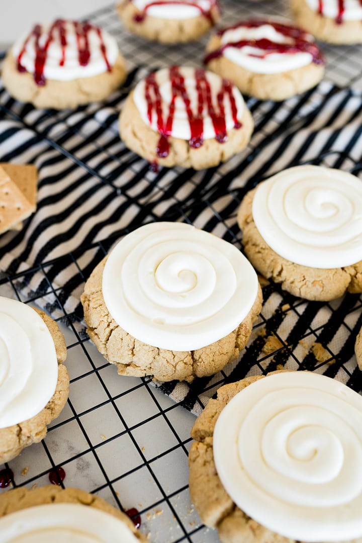 Graham cracker cookie with a swirl of cheesecake frosting and some cookies drizzled with raspberry preserves, all on a cooling rack