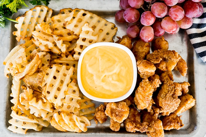 copycat chick fil a nuggets on a pan with waffle cut fries, dipping sauce and purple grapes