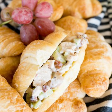 chicken salad inside of a croissant, with grapes and celery around it.