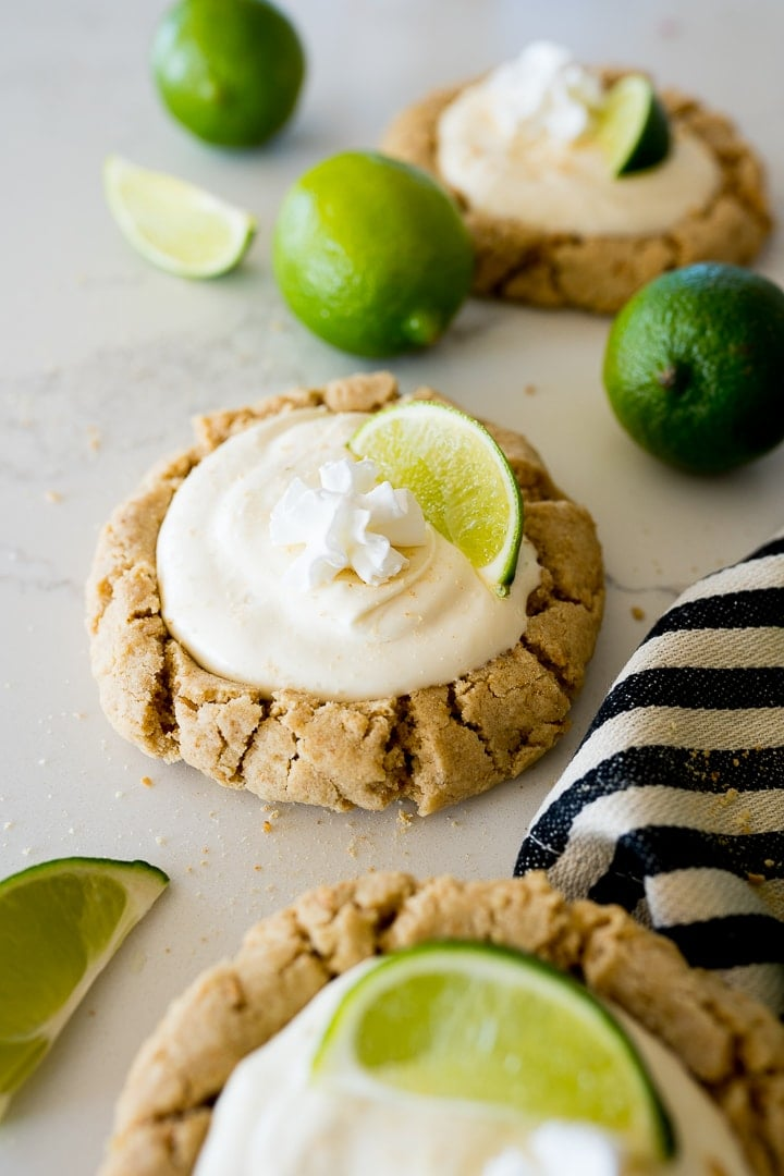 crumbl copycat key lime pie cookies with lime slices on the counter