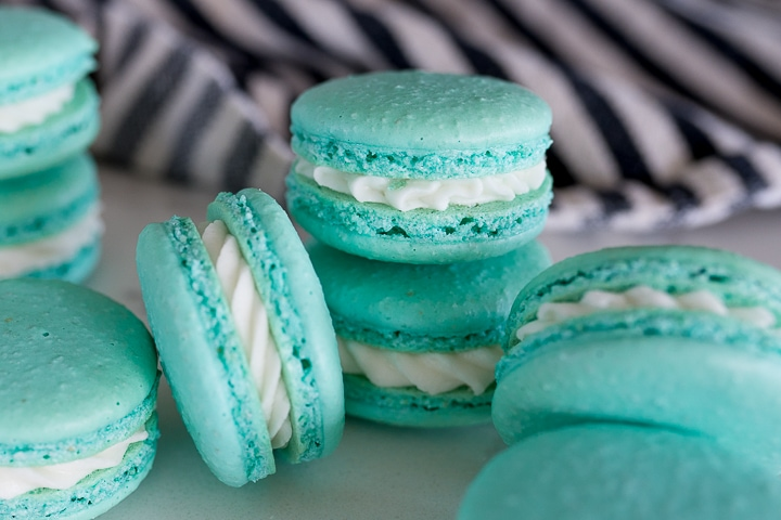 blue macarons stacked on top of each other on a white backdrop with a black and white striped towel