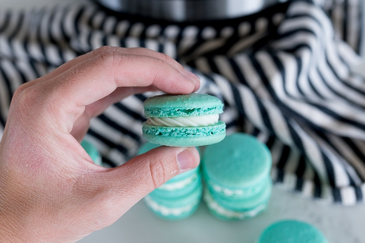 French macarons being held in a hand