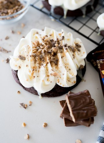 Chocolate heath cake cookie on the counter with heath bars by it