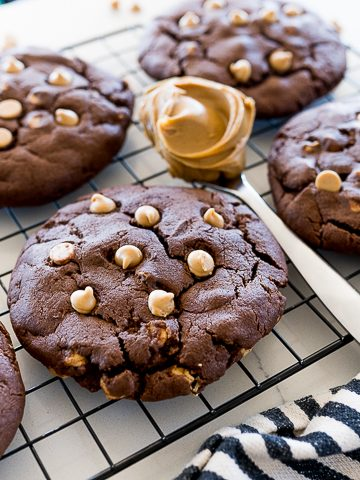 chocolate cookies with peanut butter chips on a black cookie rack