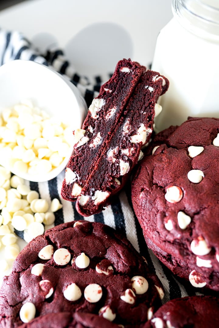 Red Velvet White Chip Cookies cut in half, with white chocolate chips