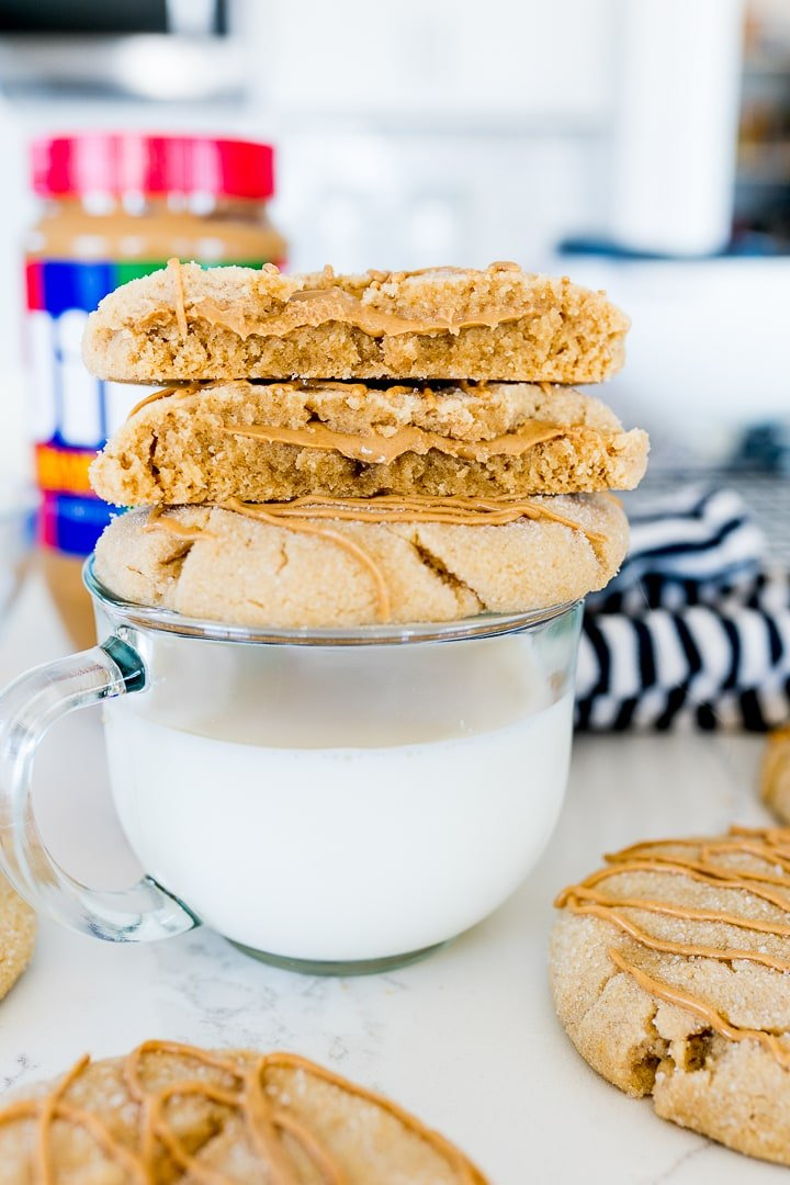 Ultimate peanut butter cookie broken in half, stacked onto a whole cookie on a glass of milk