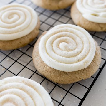 snickerdoodle cupcake cookies on a cooling rack with swirled frosting and cinnamon and sugar